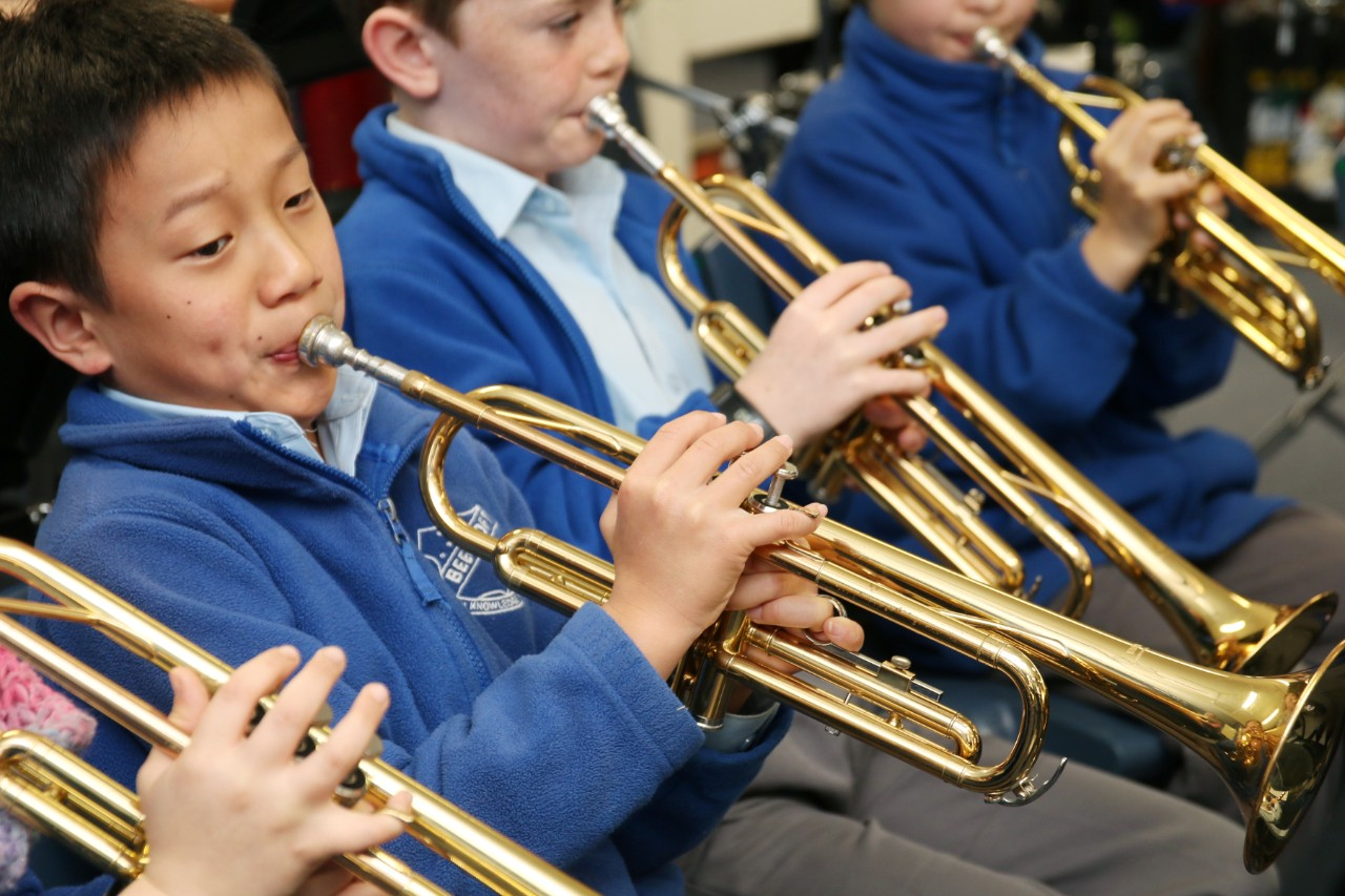 Students playing trumpets in the school band.