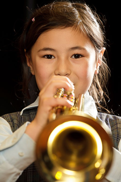 A girl with a cheeky smile plays a shiny brass trumpet.